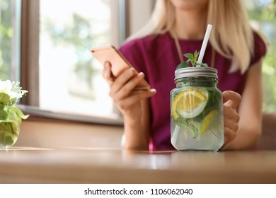 Young woman using mobile phone while drinking tasty natural lemonade at table, closeup. Detox drink