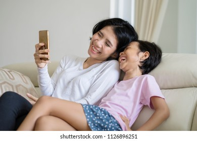 Young woman using a mobile phone while laughing with her daughter on the couch
