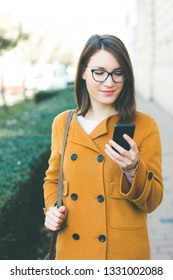 Young woman using mobile phone outdoors texting