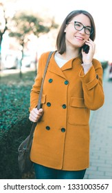 Young woman using mobile phone outdoors on street calling