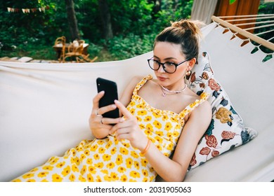 Young woman using mobile phone, relaxing in hammock outdoors, in the backyard garden.