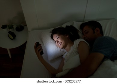 Young woman using mobile phone, while husband asleep