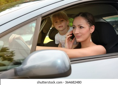 Young woman using mobile phone during driving a car, her daughter standing back, don't using safety seat ,Unsafe drive on the road!