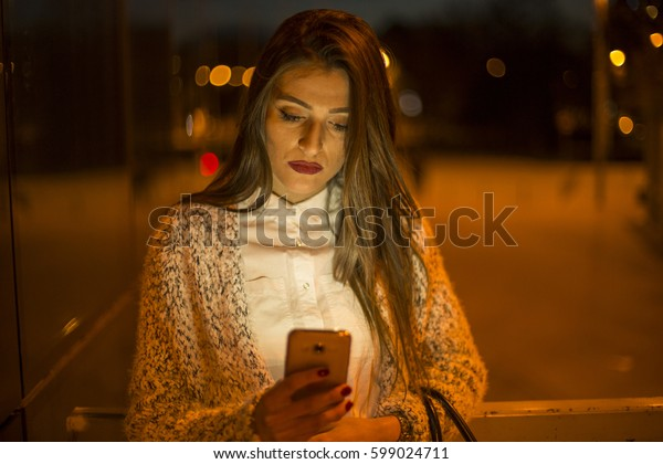 Young woman using mobile phone in night