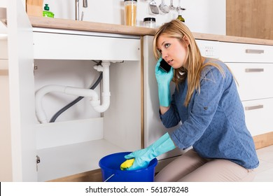 Young Woman Using Mobilephone For Emergency Plumber Call To Fix Water Drain Leak