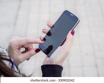 Young woman using modern smartphone with blank screen