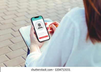 young woman using new smartphone with face id technology
