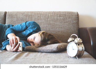 Young woman using phone in bed, looking at screen, insomnia, check time, wake up with smartphone, mobile phone addiction - alarm clock near