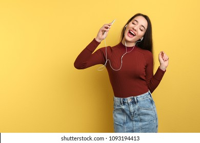 Young woman using phone for listening to music on color background