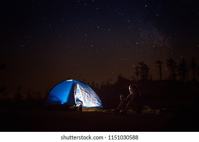 Young woman using phone on night camp on mountain trail. Szczyrk, Beskidy Mountains, Poland