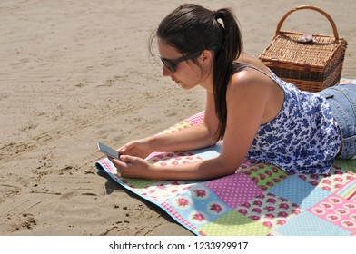young woman using phone whilst lying on beach.