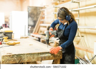 Young woman using a screwdriver on a piece of wood while working in a woodshop