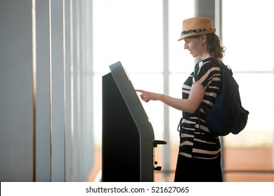 Young woman using self service machine in transfer area, doing self check in or buying plane tickets at automated machine with touchscreen interactive display in modern airport terminal building