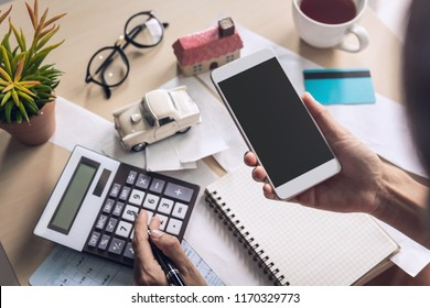 Young woman using smart phone and checking bills, taxes, bank account balance and calculating expenses in the living room at home