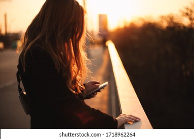 Young woman using smart phone while holding railing standing on bridge in city at sunset