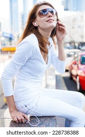 Young woman using a smart phone outdoors / photography of young Caucasian woman wearing sunglasses