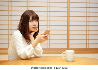 Young woman using a smart phone or cell phone at home