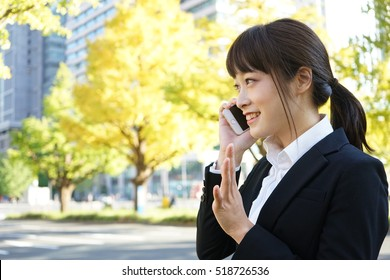Young woman using a smart phone on the street