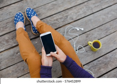 young woman using smart phone at wooden back