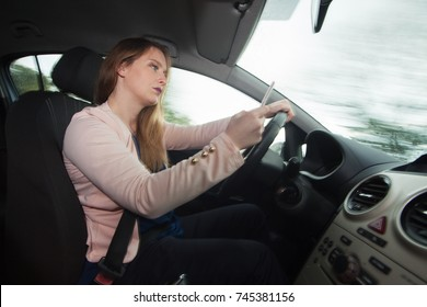 Young woman using smart phone while driving a car