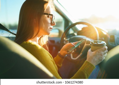 Young woman using smartphone and drinking coffee while sitting in a car