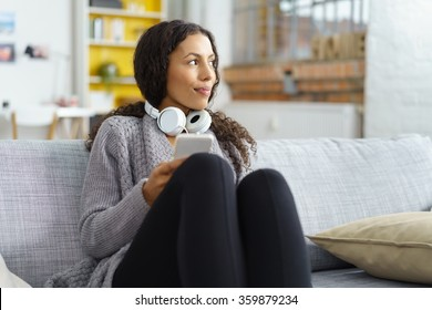 Young woman using smartphone at home with earphones while looking out of the windows