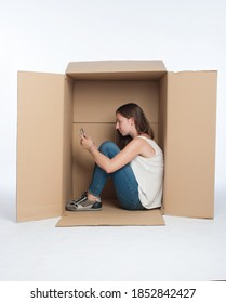 young woman using smartphone inside a Box isolated on white