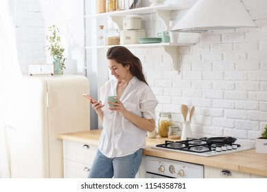 Young woman using smartphone leaning at kitchen table with coffee mug and organizer in a modern home. Smiling woman reading phone message. Brunette happy girl typing a text message