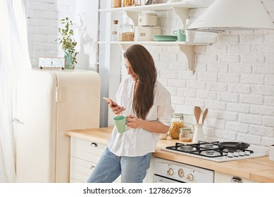 Young woman using smartphone leaning at kitchen table with coffee mug and organizer in a modern home. Smiling woman reading phone message.