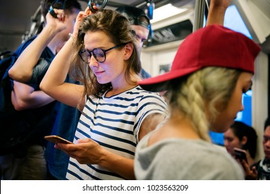 Young woman using a smartphone on the subway