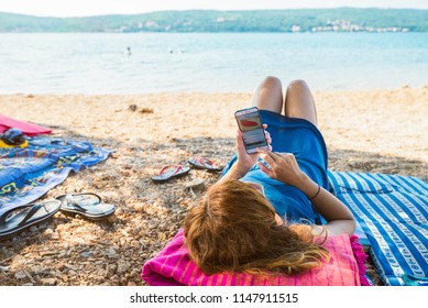 Young woman using a smartphone on the beach with the sea in the background. Young woman on summer vacation on island Krk, Croatia.