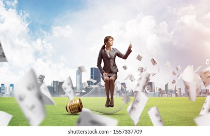 Young woman using smartphone on green field with falling paper documents. Pretty girl sitting on big glowing lamp. Businesswoman chatting with phone. Business statistics and analytics.
