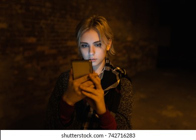 Young woman using smartphone on the street by night.