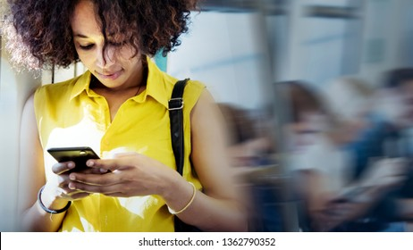 Young woman using a smartphone in a subway