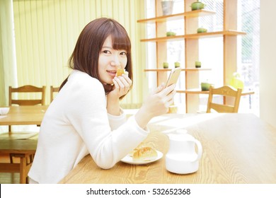 Young woman using a smartphone while eating breakfast