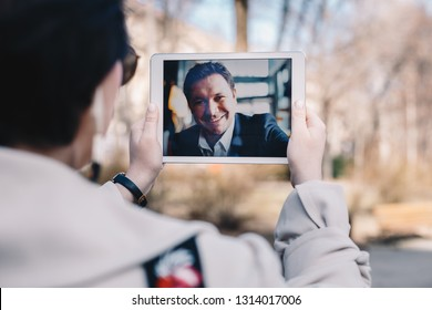 Young woman using a tablet by having a video call chat with her businessman boyfriend who is away on a business trip. Concept of keeping a long distant relationship in a career oriented world. - Shutterstock ID 1314017006