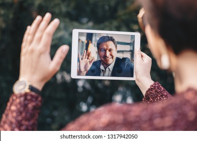 Young woman using a tablet by having a video call chat with her businessman boyfriend who is away on a business trip. Concept of keeping a long distant relationship in a career oriented world.