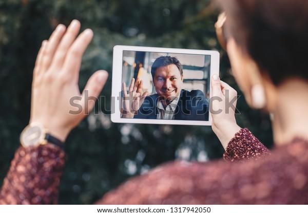 出張中のビジネスマンのボーイフレンドとビデオ通話でタブレットを使う若い女性。キャリア志向の世界で長い距離を置く関係を保つという考え方。