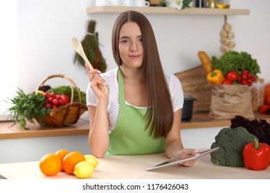 Young woman using tablet computer while cooking in kitchen. Householding, tasty food and digital technology in lifestyle concepts