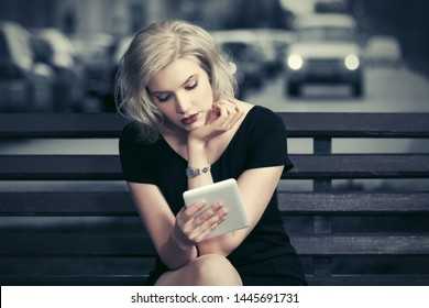Young woman using tablet computer sitting on bench Stylish blonde fashion model in black dress