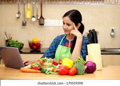 Young woman using a tablet computer in her kitchen
