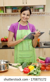 Young woman using a tablet in her kitchen