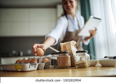 Young woman using tablet in kitchen where read cake recipe