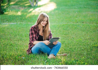 Young woman using tablet outdoor sitting on grass, smiling.