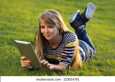 young woman using a tablet outdoors