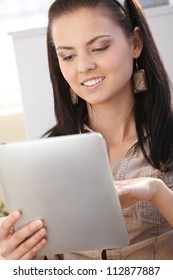 Young woman using tablet PC, smiling at home.