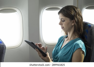 Young woman using a tablet/ipad on a plane