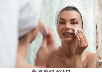 Young woman is using a toner for her complexion
