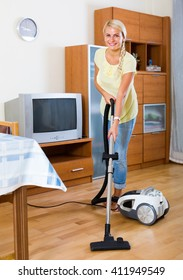 Young woman using vacuum cleaner during regular clean-up