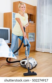 Young woman using vacuum cleaner during regular clean-up in the flat